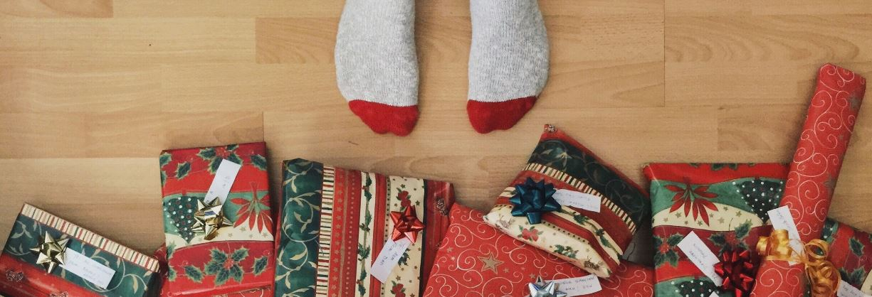 child's feet standing close to Christmas tree where gifts are piled
