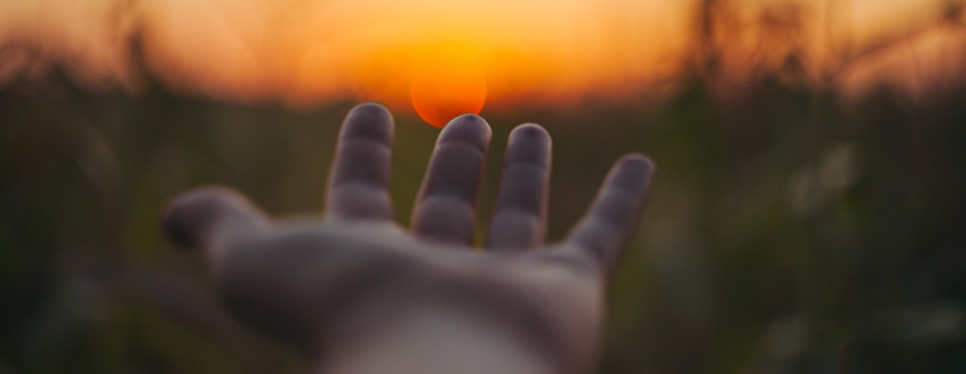 suicide prevention - hand reaching toward setting sun