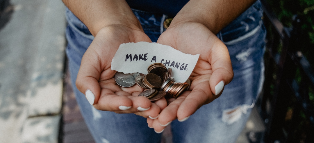 """handful of coins with sign that says """"make a change"""""""