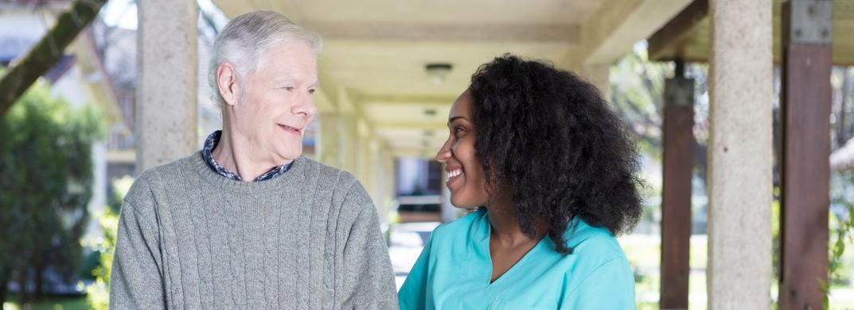 African American nurse assisting elderly man outdoors