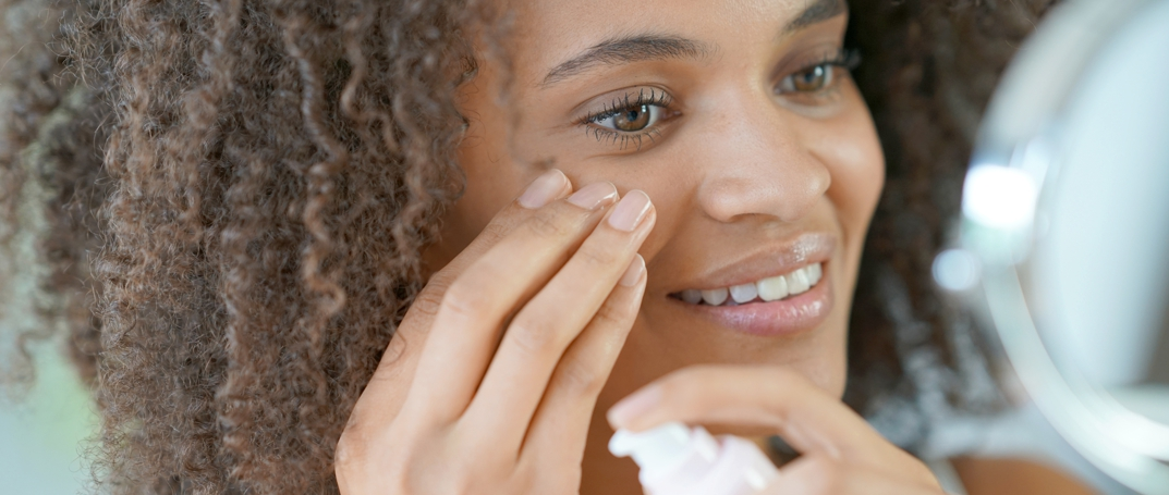young woman applying lotion to face