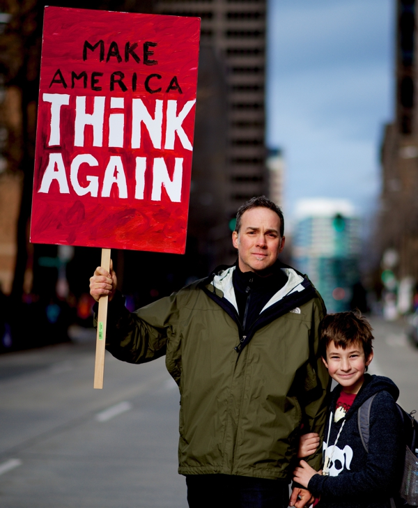 """father and son holding sign that reads """"make america think again"""""""