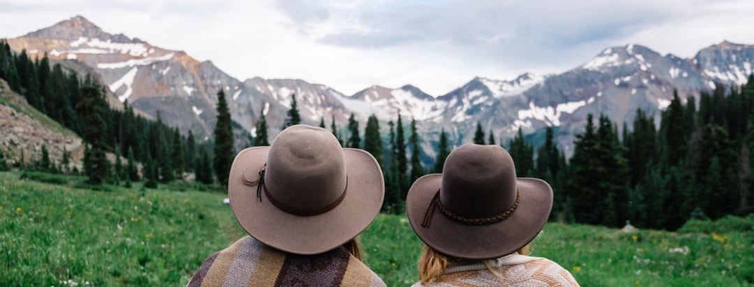 Two women looking across meadow at snow-capped mountains