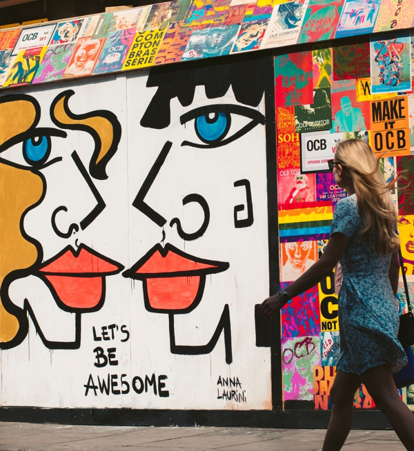 "woman walking in front of mural that says ""let's be awesome"""