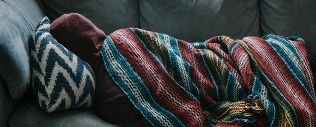 youth lying on couch with striped cover