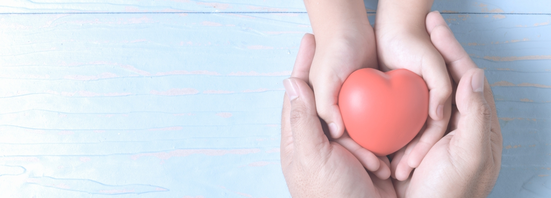 adult and child hands holding red heart on vintage tone, health care, love and family insurance concept, world heart day