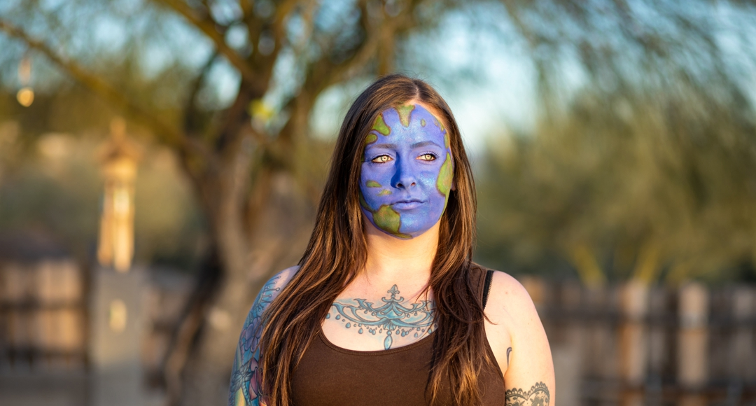 photo by Nicci Radhe - woman outdoors with earth painted on face