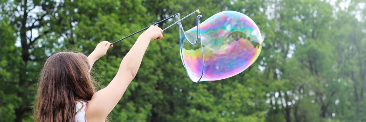 small girl outdoors blowing bubbles
