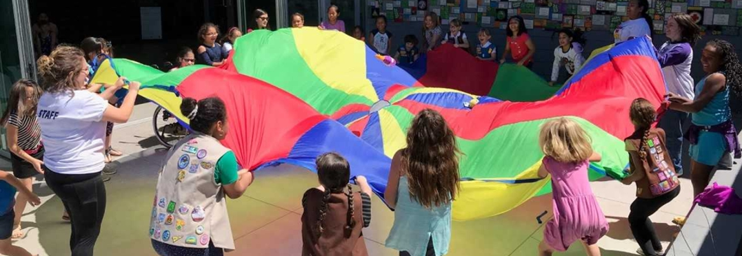 Girl Scouts circling parachute
