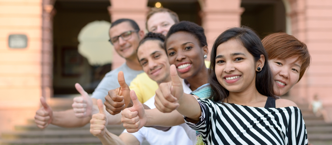 Smiling diverse group of young people in row giving thumbs up sign