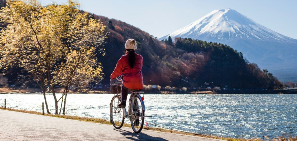 woman riding bicycle beside lake with mountain in the background