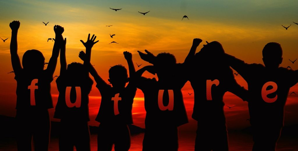 "children with arms raised looking facing sunset with the word ""future"" spelled out across their backs"