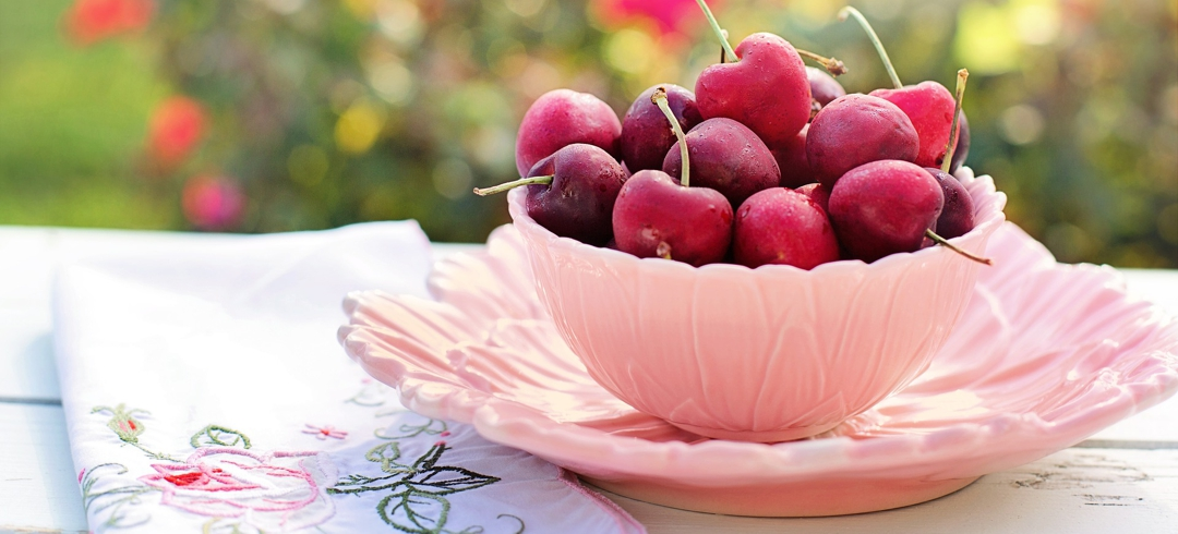 pink bowl full of cherries outdoors with embroidered napkin