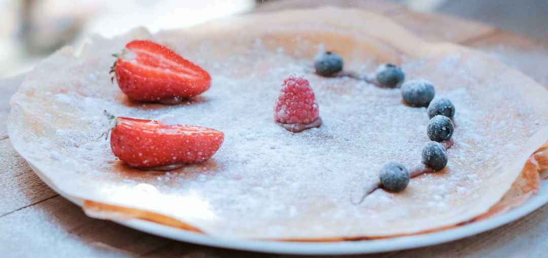 crepe on dinner plate with smiley face made from strawberry slices and blueberries and powdered sugar