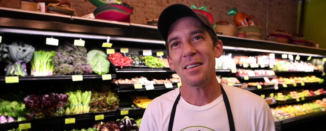 Employee in produce department inside Food Conspiracy Co-op