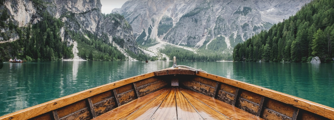 front of wooden boat on a beautiful mountain lake