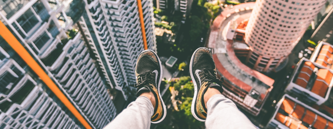 feet with sneakers hanging off the edge of a very tall building