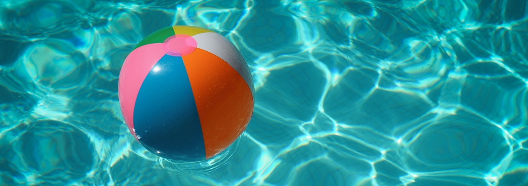 Beach ball floating in outdoor swimming pool