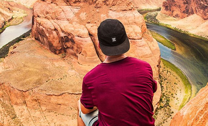young man with back to camera sitting at edge of Grand Canyon with Colorado River below