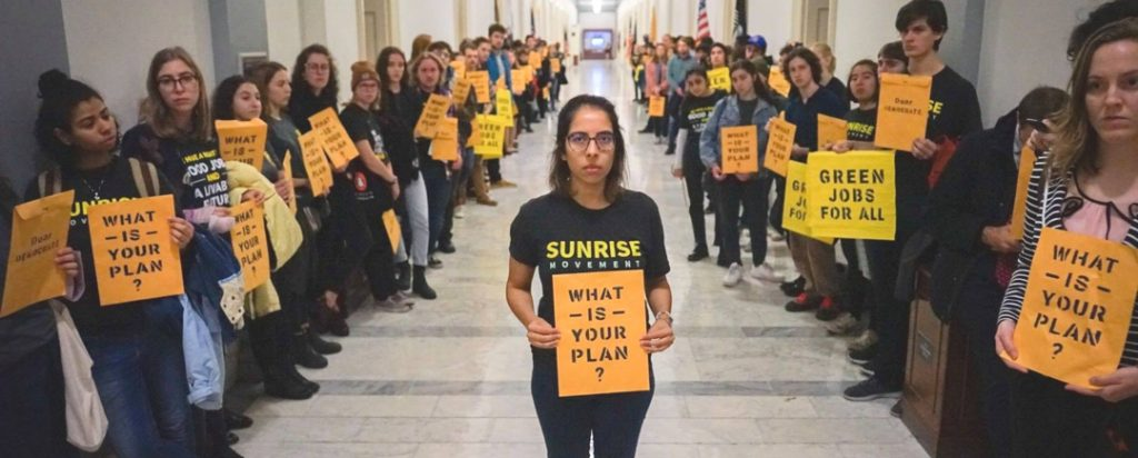 """large group of Sunrise Movement youth activists carrying signs that say """"What is your plan?"""""""