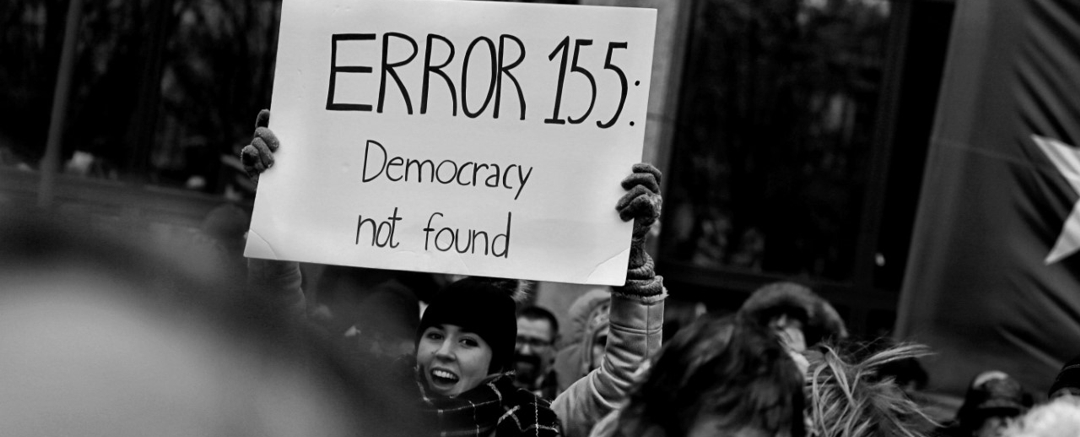 woman at rally holding sign that reads: Error 155: Democracy not found
