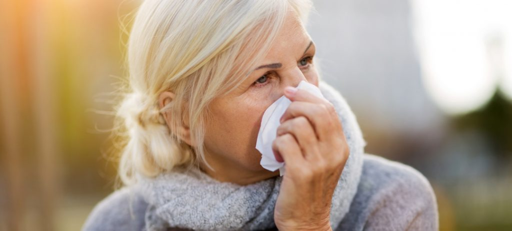 Woman outdoors holding tissue to her nose