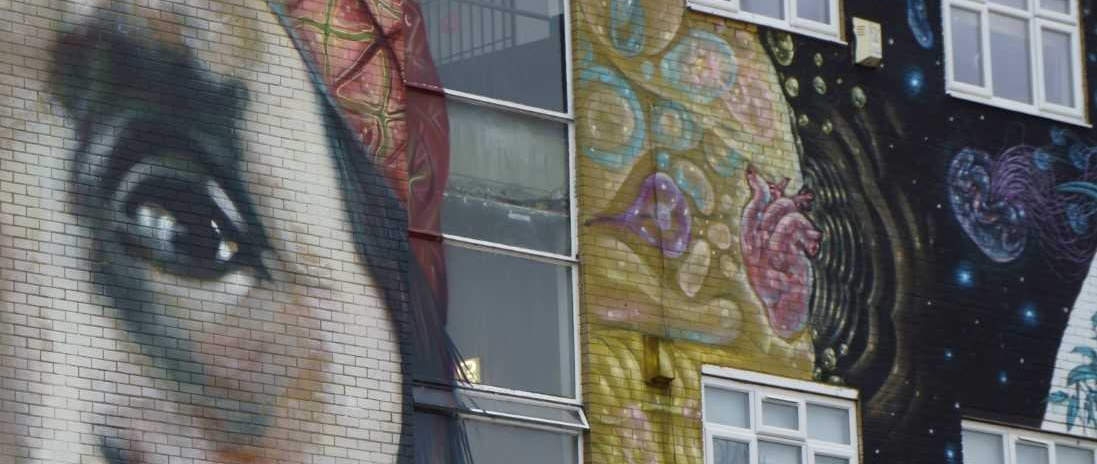 mural of Native American and graphic images painted on outside of building