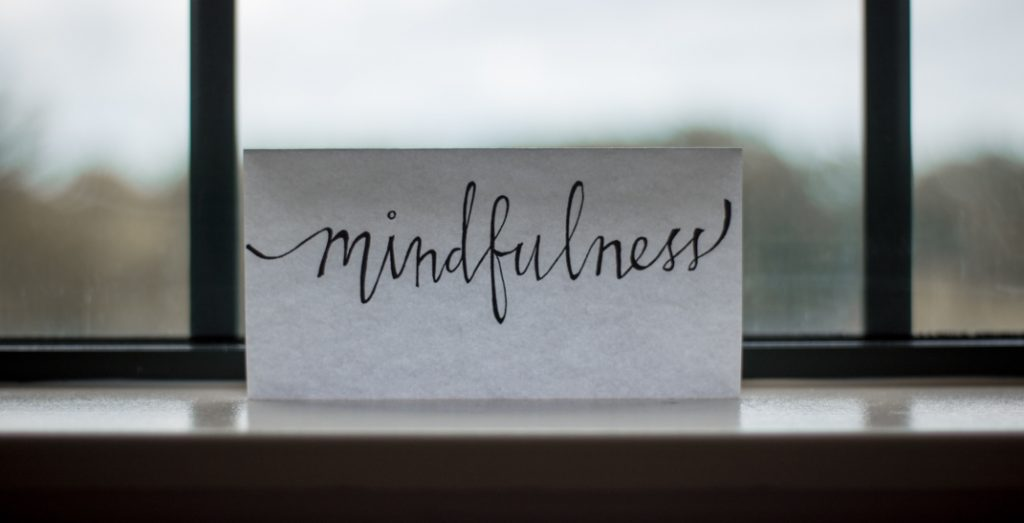 "the word ""mindfulness"" written on a piece of paper propped against a window"