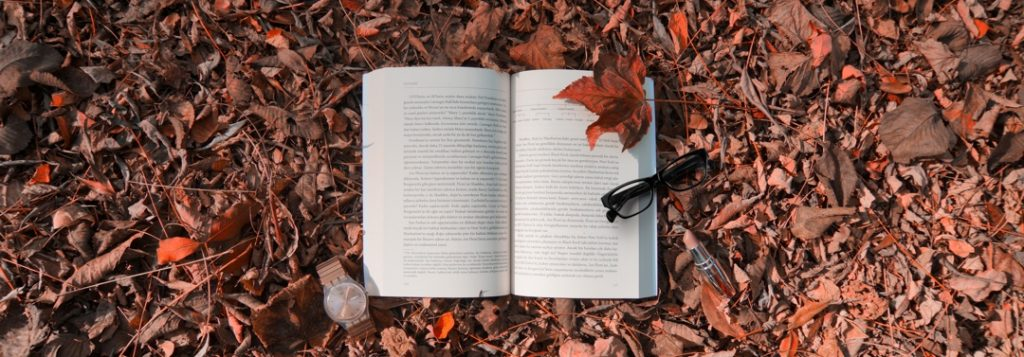 open book outdoors lying in fallen autumn leaves with a pair of glasses and wrist watch