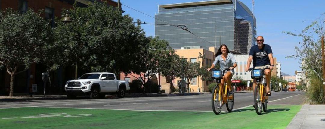 Man and woman riding Tugo Bike Share bicycles downtown Tucson, AZ