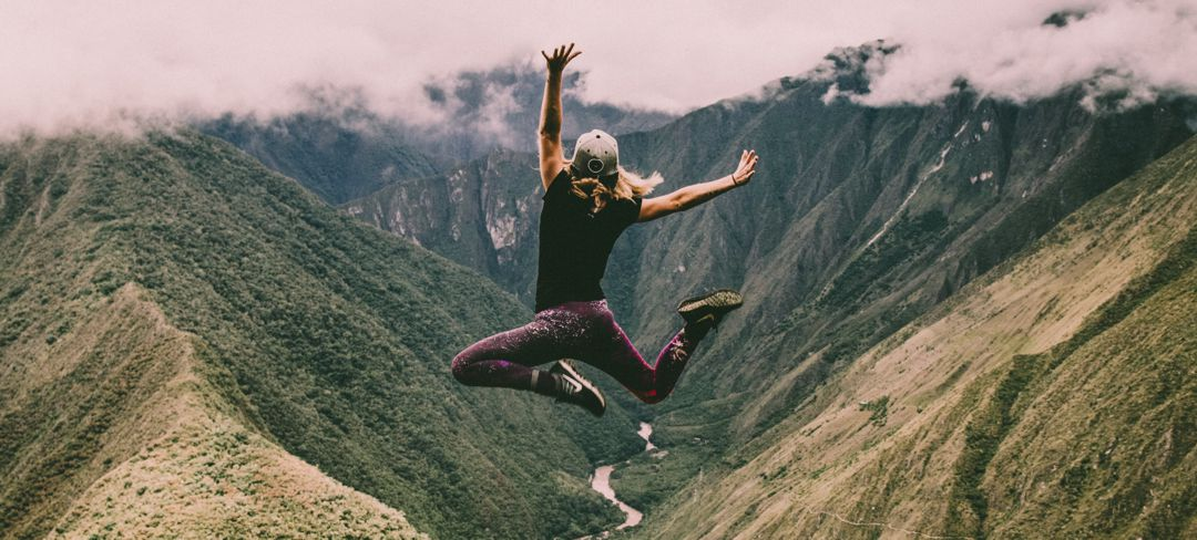 Young woman jumping high in the air with canyon and river in background