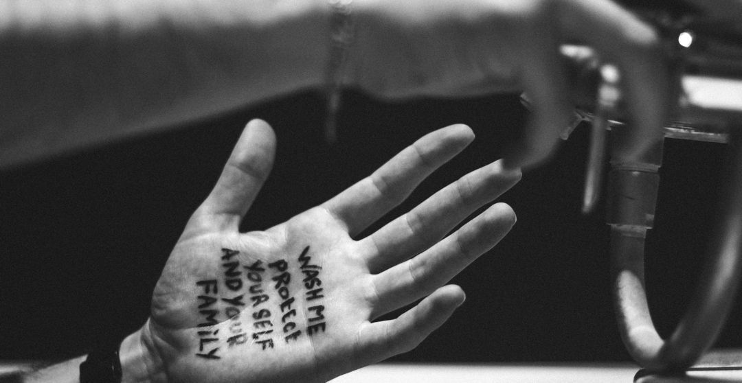 """black and white photo of hand with the words """"wash me protect yourself and your family"""" on the palm"""