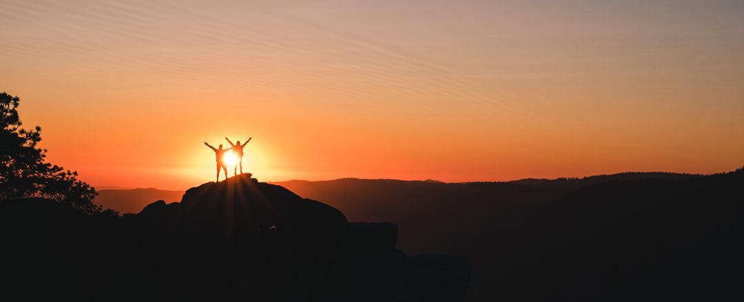 two people standing with arms raised at the top of a knoll silhouetted against the sun
