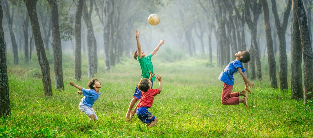 boys playing soccer, jumping for the ball,  in a grassy forest