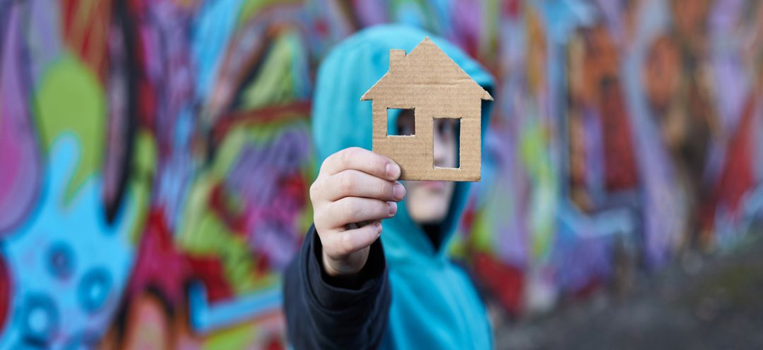 young boy holding a cardboard house
