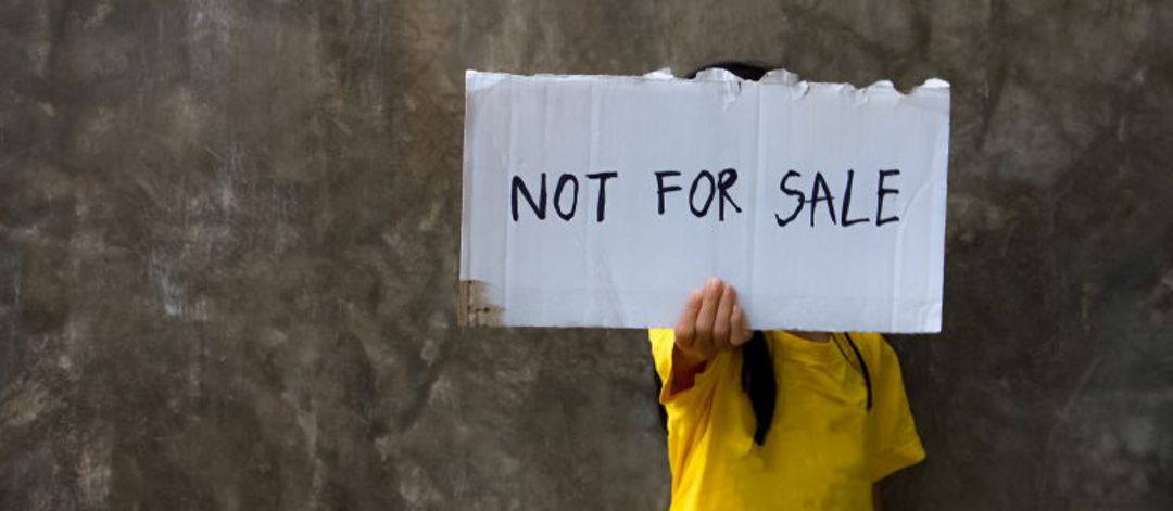"young girl holding sign in front of face that says ""not for sale"""