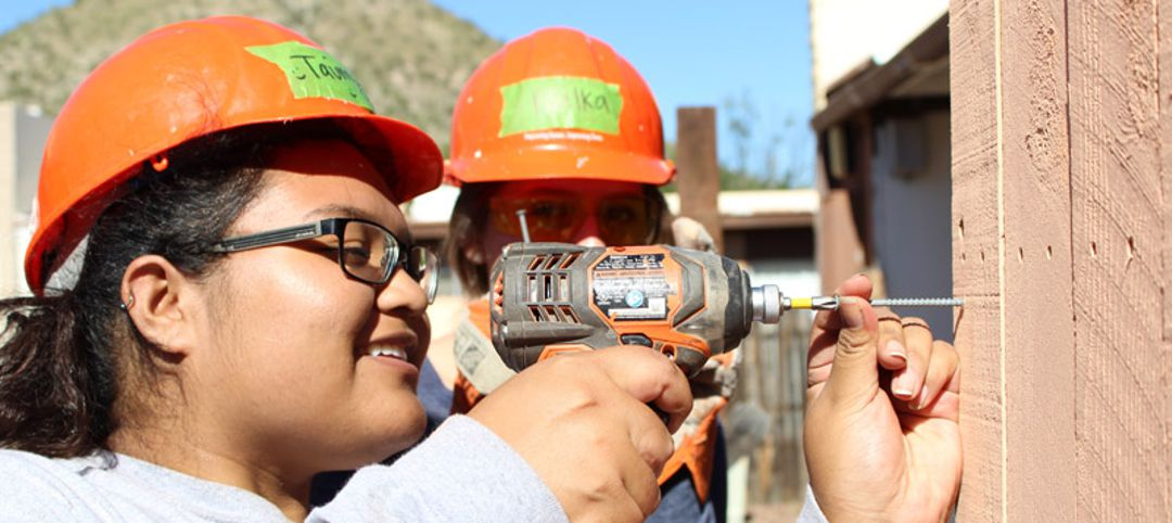 young woman using drill at a home building site with another woman watching