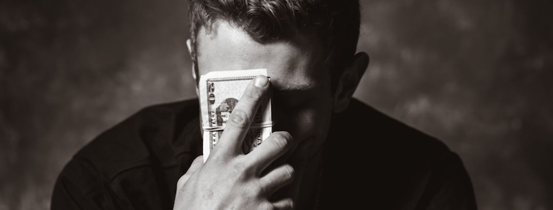 man with head tipped down holding hand to forehead with money in his hand looking worried