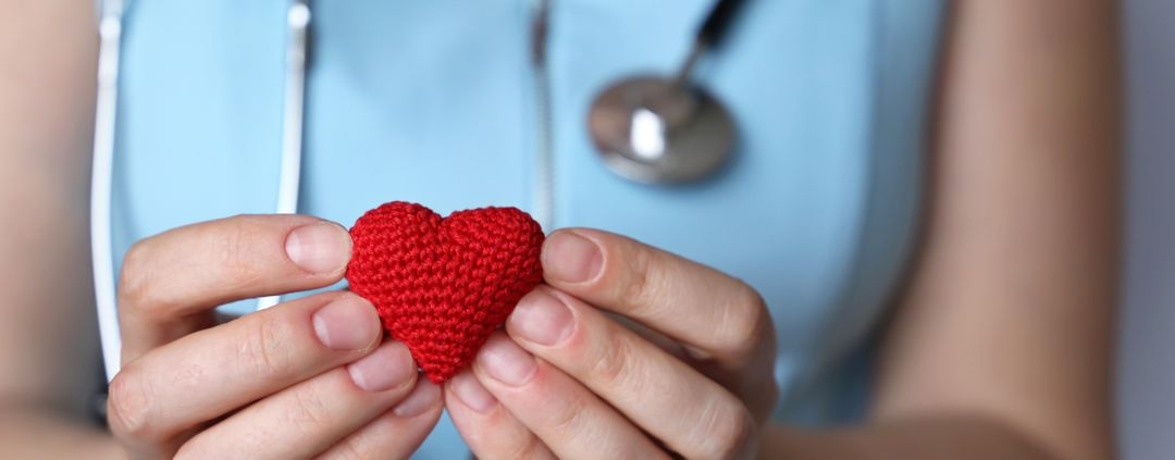 woman nurse or doctor with stethoscope holding red knitted heart in hands