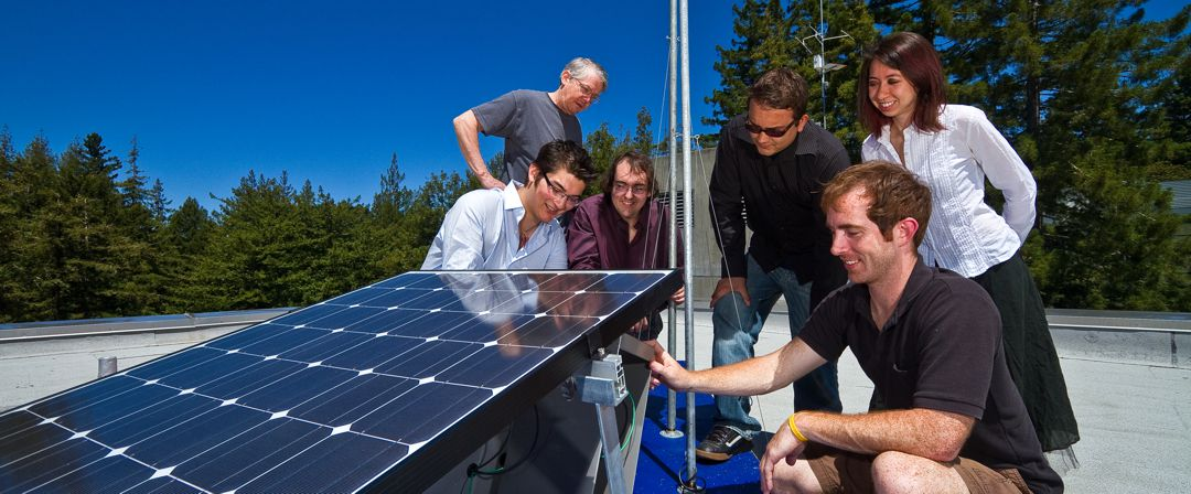 group of men and women on the roof of a home looking at a solar panel