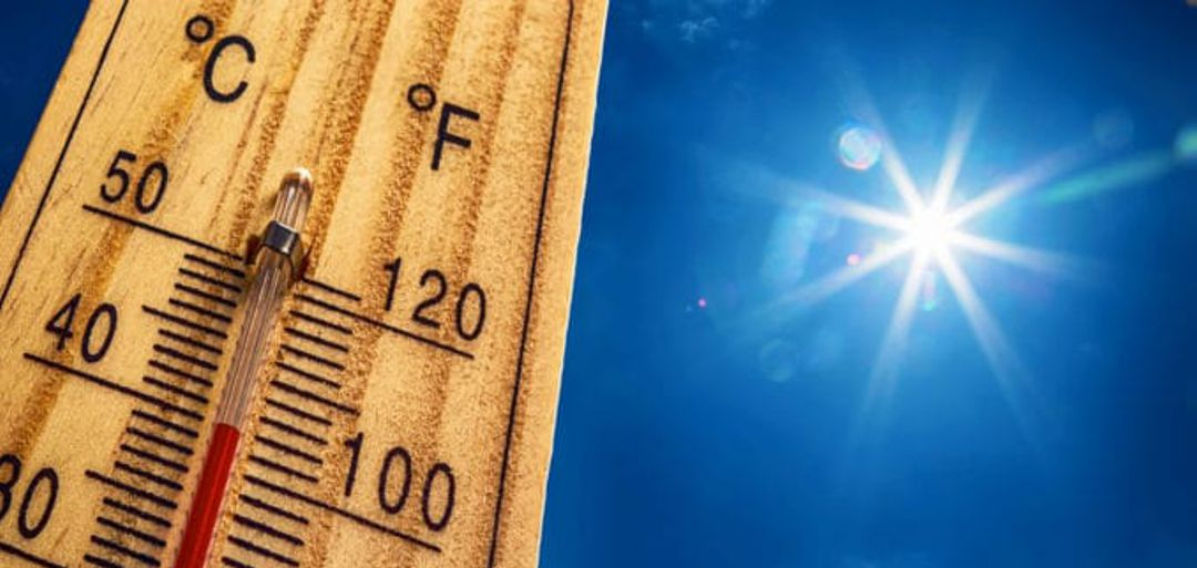 Photo of outdoor temperature gauge against blue sky and sun