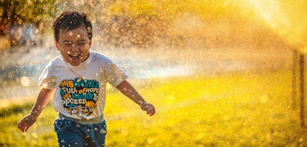 little boy running through sprinkler
