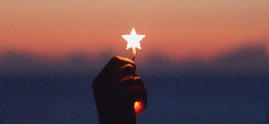 glowing star being held in hand agains a sunset sky