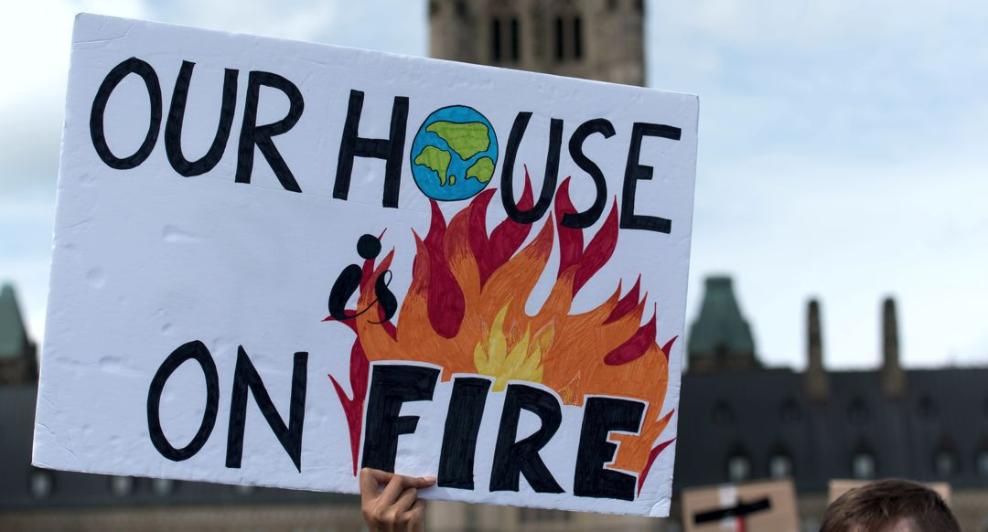 Hand held sign that says Our House is on Fire