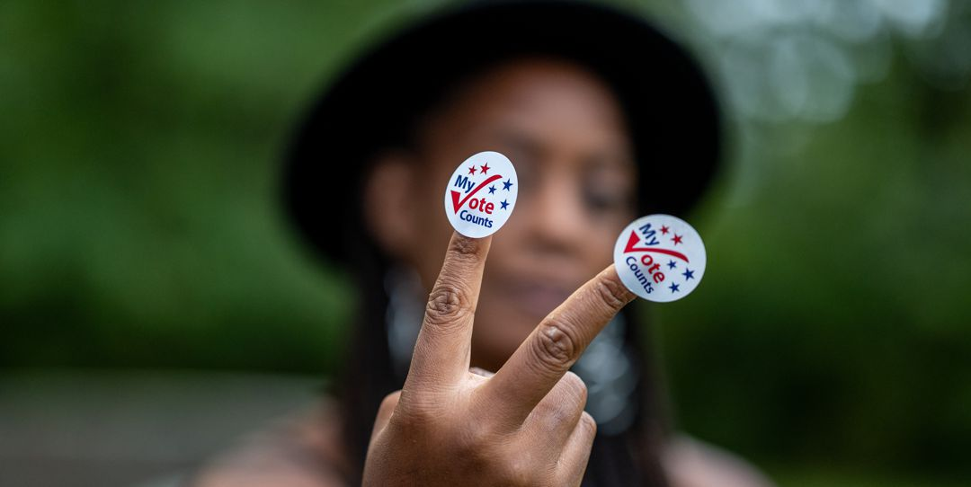 "Young black adult wearing stickers on her fingers that say ""my vote counts"""