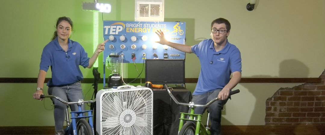 Two students on stationary bicycles, generating electricity while pedaling