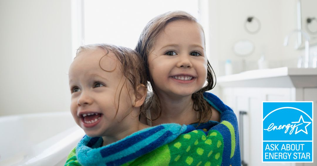 Two little girls wrapped in one big towel after bathing