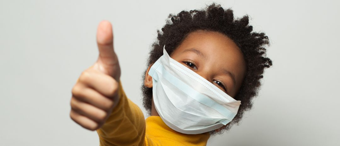 Happy African American black kid in medical protective face mask showing thumb up on white