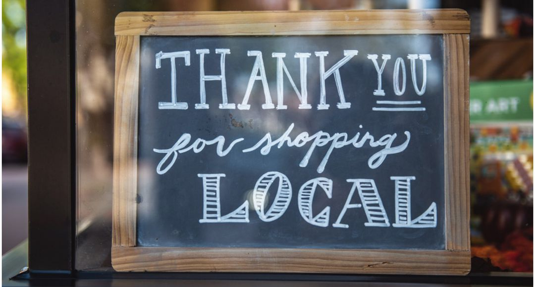 """sign in window that says """"thank you for shopping local"""""""