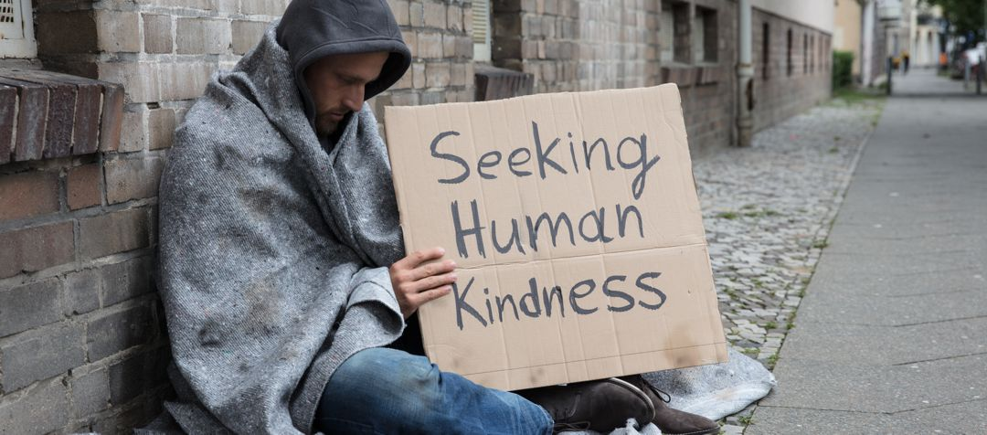 "Homeless man sitting on ground leaning against brick wall holding a sign that says ""seeking human kindness"""